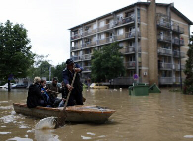 People paddle a boat on a flooded street in Obrenovac, some 30km southwest of Belgrade, Serbia.
