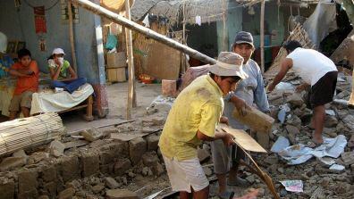 People remove bricks after a magnitude-7 earthquake hit Ica, Peru