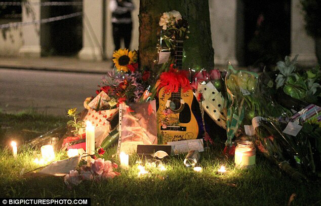 Pictures of Amy, a guitar, flowers, candles and letters were laid
