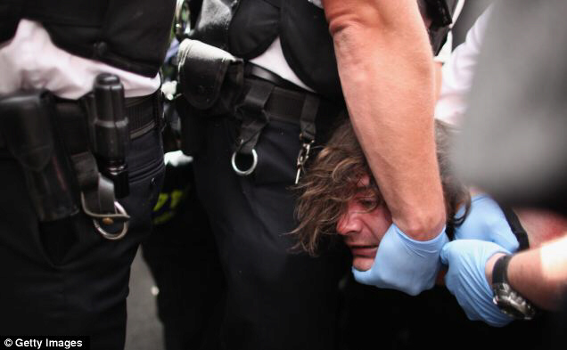 Police keep a firm hold on one of the demonstrators on a day that saw 10,000 officers have their leave cancelled