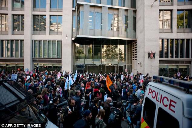 Marching on the City: Police look on as protesters walk around the perimeter of the London Stock Exchange