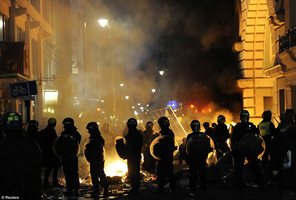 Riot: Police officers stand in front of a fire lit be demonstrators in central London