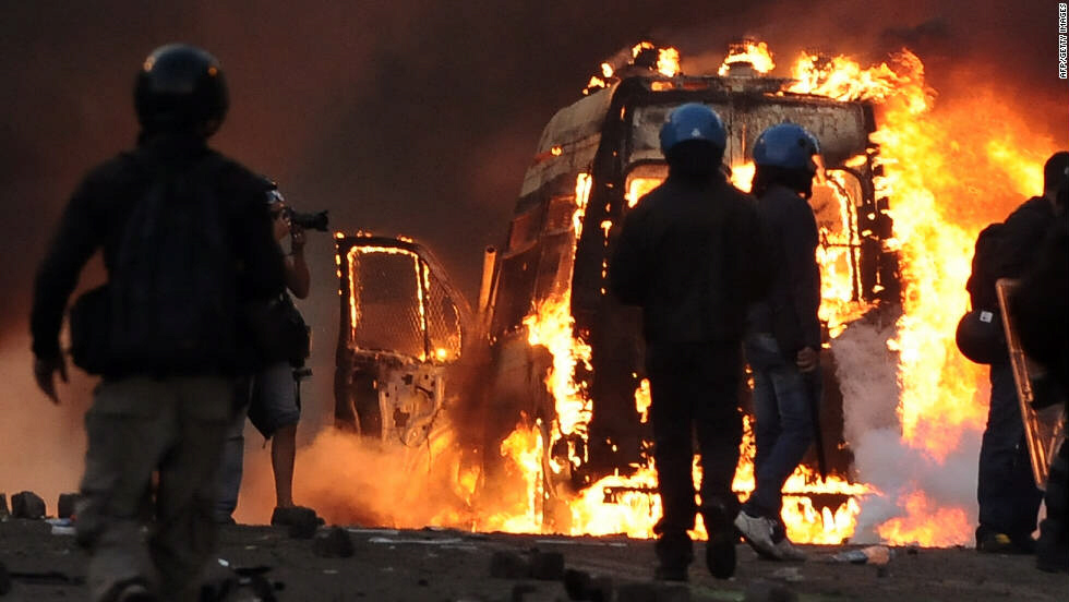Police walk past a flaming van. Police battled with water cannons while the anarchists remained armed with knives, bats, Molotov cocktails and fireworks, Newsweek correspondent Barbie Nadeau told CNN.