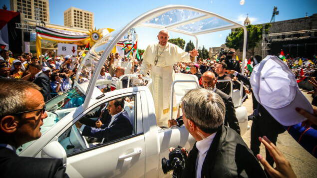 Pope Francis waving to the people after a mass in Bethlehem.