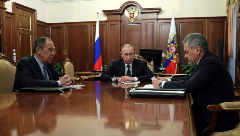 Russian President Vladimir Putin speaks with Foreign Minister Sergey Lavrov and Defense Minister Sergei Shoigu