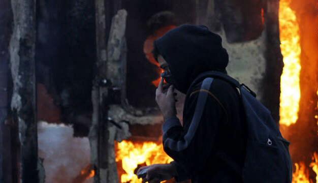 Protester covers his face  as he walks in front of burning in Athens