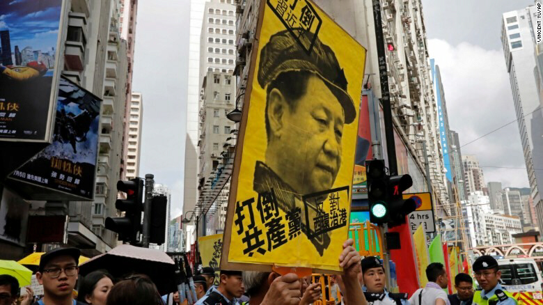 Protester raises poster of Chinese President Xi Jinping