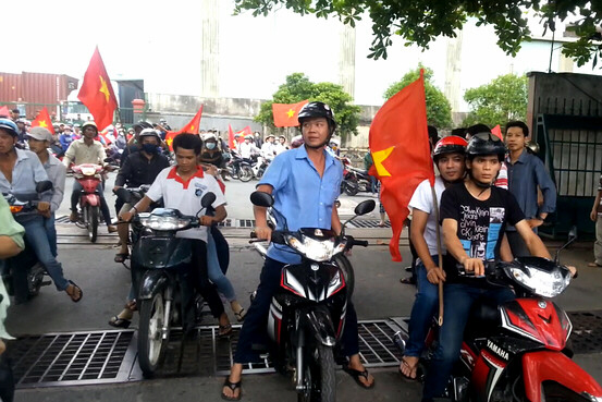 Protesters carry Vietnamese flags during an anti-China protest