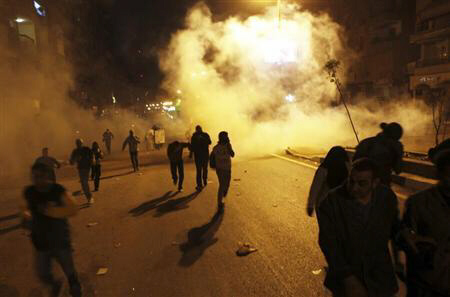 Protesters opposing Egypt President Mohamed Mursi flee teargas