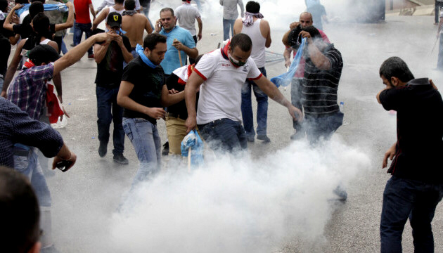 Protesters react to tear gas fired by Lebanese police officers