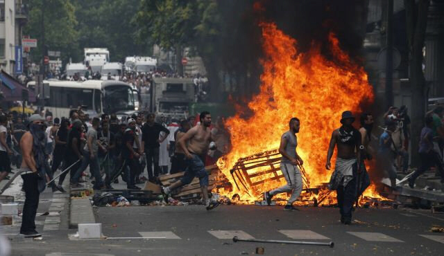 Protesters run by fire barricade in Barbes-Rochechouart in Paris
