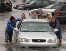 Redwood High School students push a car from a flooded parking lot at the Larkspur, California