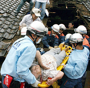 Rescuers carry an injured woman from a collapsed house in Kariwa