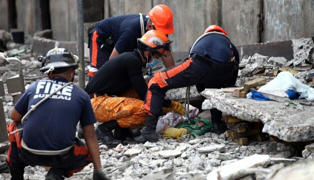 Rescuers pull a man from the rubble in Cebu