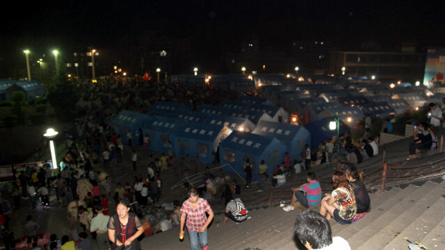 Residents rest by makeshift tents at emergency relief center