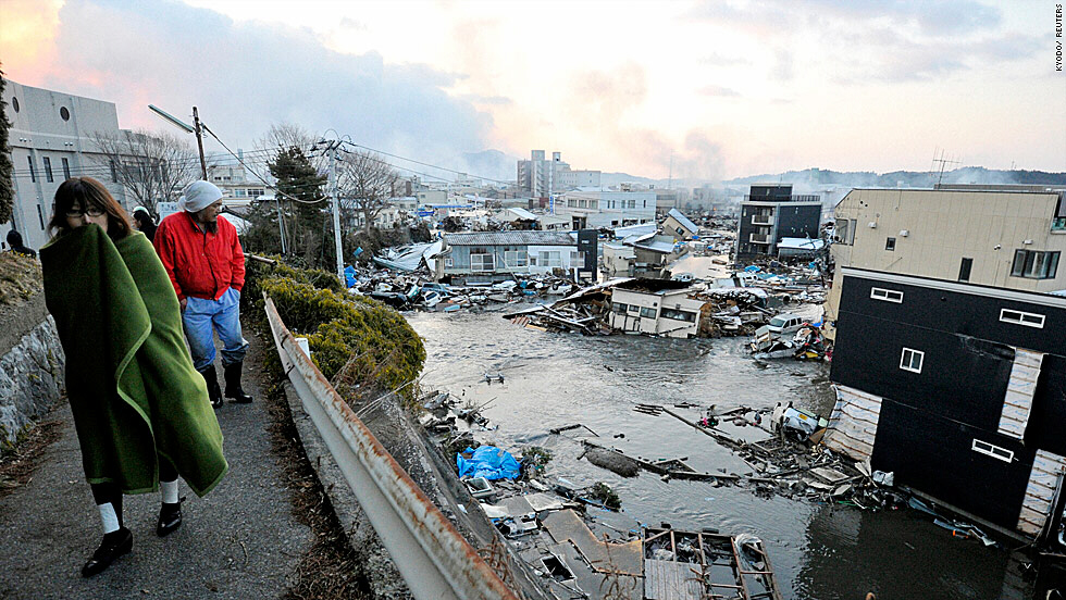 Residents walk path overlooking shattered homes in Kesen Numa