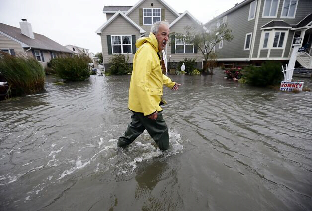 Richard Thomas walks through floodwaters in Fenwick Island, Del