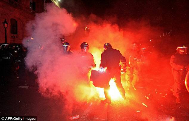 Riot police deal with a hail of flares thrown by protesters