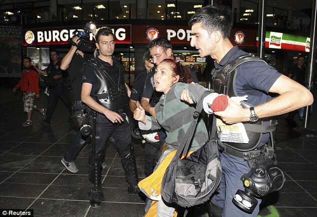 Riot police detain female protester during demonstrations