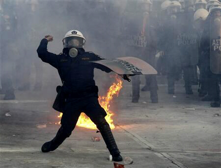 Riot police officer throws stone at demonstrators during violent protests in Athens