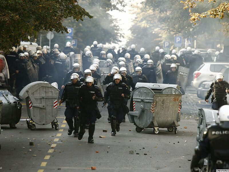 Riot police run down a street during clashes in Belgrade