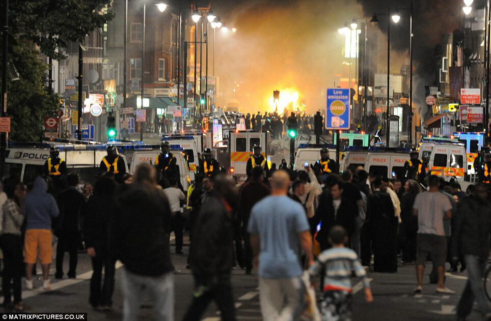 Out of control: Scores of police tackle rioters in Tottenham Saturday night