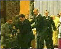 Security guards block a man as he rushes Pope John Paul II