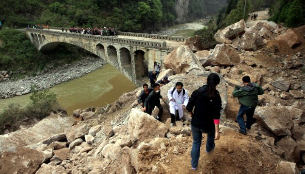 Survivors make their way along damaged area in Lushan