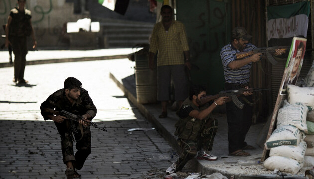 Syrian rebels prepare to fire during clashes with regime forces