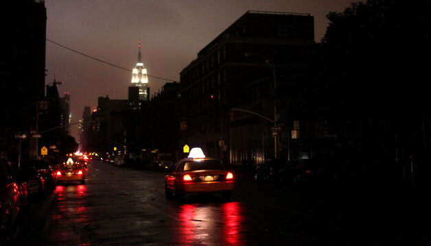 Taxis drive down New York street where power was out late Monday