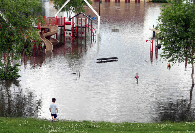 The rising Mississippi River covered a playground and roads in St. Paul