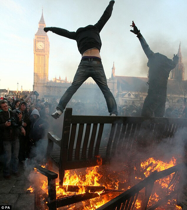 Two demonstrators jump from the top of a bonfire