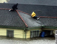 Two residents take refuge on their rooftop