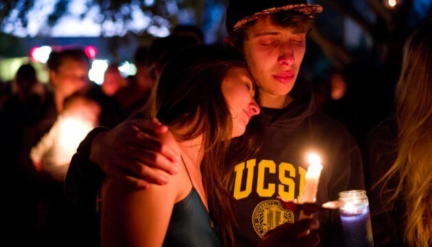 Two students comfort each other during a candlelight vigil
