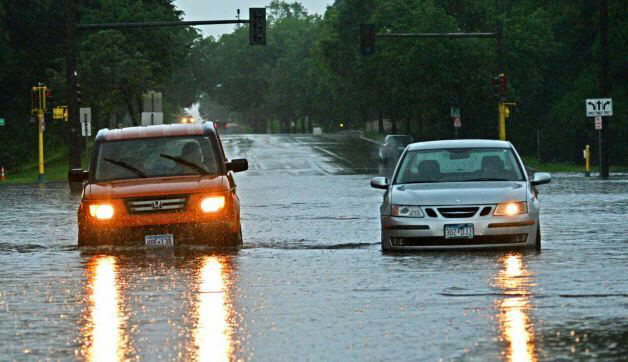 Vehicles are caught in street flooding in Minneapolis, Minn.