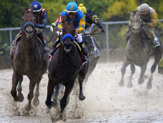Victor Espinoza aboard American Pharoah leads the pack at Preakness