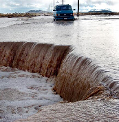 Water pours over a washed-out section of road Monday, Jan. 10, 2005.