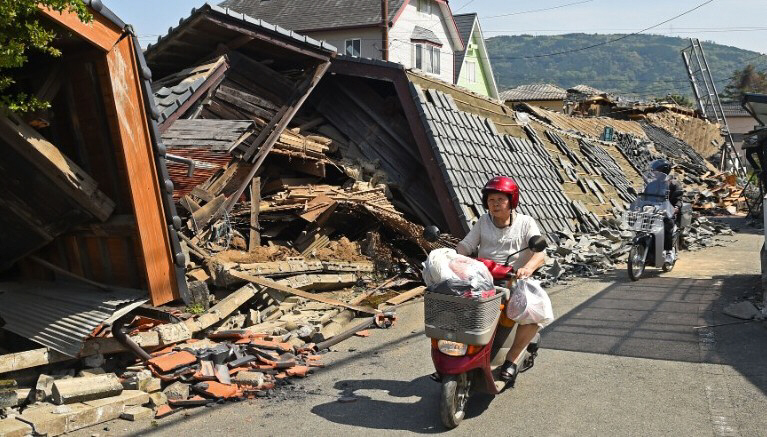 Woman rides scooter in front of collapsed house in Mashiki