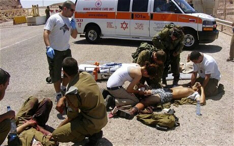 Wounded Israeli soldiers are treated at the site of a shooting attack along the border between Israel and Egypt, southern Israel, Thursday, Aug. 18, 2011.