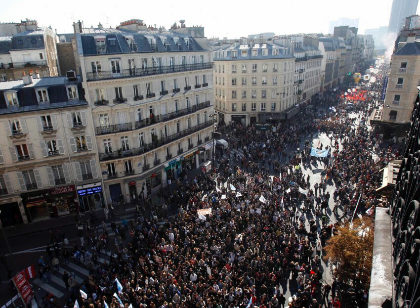 Demonstrators walk through the streets of Paris on Tuesday. Workers tried to shut down France with strikes affecting airports, public transporation, schools and the postal service in a showdown with President Sarkozy over his retirement reform plans.